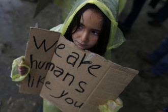 A migrant girl shows a banner during a protest demanding the opening of the border between Greece and Macedonia in the northern Greek border station of Idomeni, Greece, Wednesday, March 23, 2016.  The U.N. refugee agency pulled out staff Tuesday from facilities on Lesbos and other Greek islands being used to detain refugees and migrants as an international deal with Turkey came under further strain. (AP Photo/Darko Vojinovic)